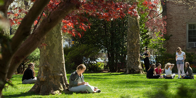 Photo of student outside on the lawn on campus